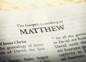 A copy of the Bible is open to the title page of ther first book of the New Testament, the Gospel according to Matthew.