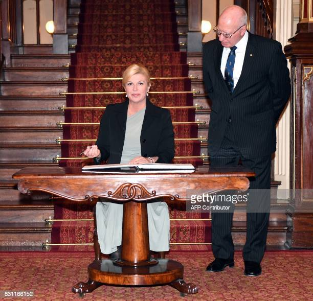 The Governor of New South Wales David Hurley looks on as Croatia's President Kolinda GrabarKitarovic signs the visitor's book at Government House in...