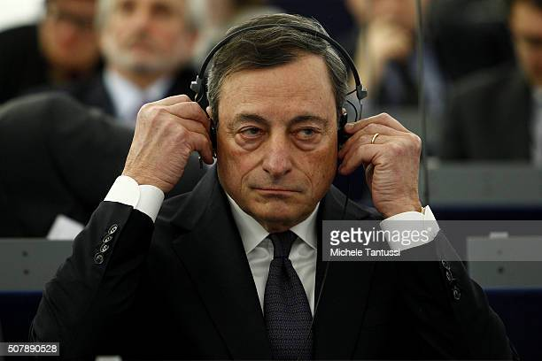 The governor of the European central Bank or ECB Mario Draghi adjusts his earphones in the plenary room in the European Parliament ahead of the...