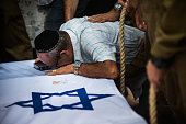 The grandfather of Israeli soldier Jordan Bensimon cries over his casket during his funeral on July 22 2014 in Ashkelon Israel Bensimon was 22 and...
