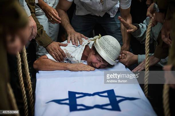 The grandmother of Israeli soldier private first class Jordan Bensimon cries over his casket during his funeral on July 22 2014 in Ashkelon Israel...