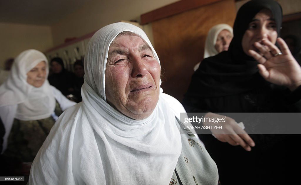 The grandmother (C) of Naji Balbisi, a 19-year-old Palestinian shot by Israeli troops, mourns with other relatives during his funeral in the West Bank town of Anabta near Tulkarem on April 4, 2013. The West Bank simmered with anger as thousands joined the funeral of prisoner Maisara Abu Hamdiyeh who died in an Israeli jail and similar numbers gathered to bury two teens shot dead overnight during clashes over the death of the prisoner, Israeli and Palestinian sources said. AFP PHOTO / JAAFAR ASHTIYEH