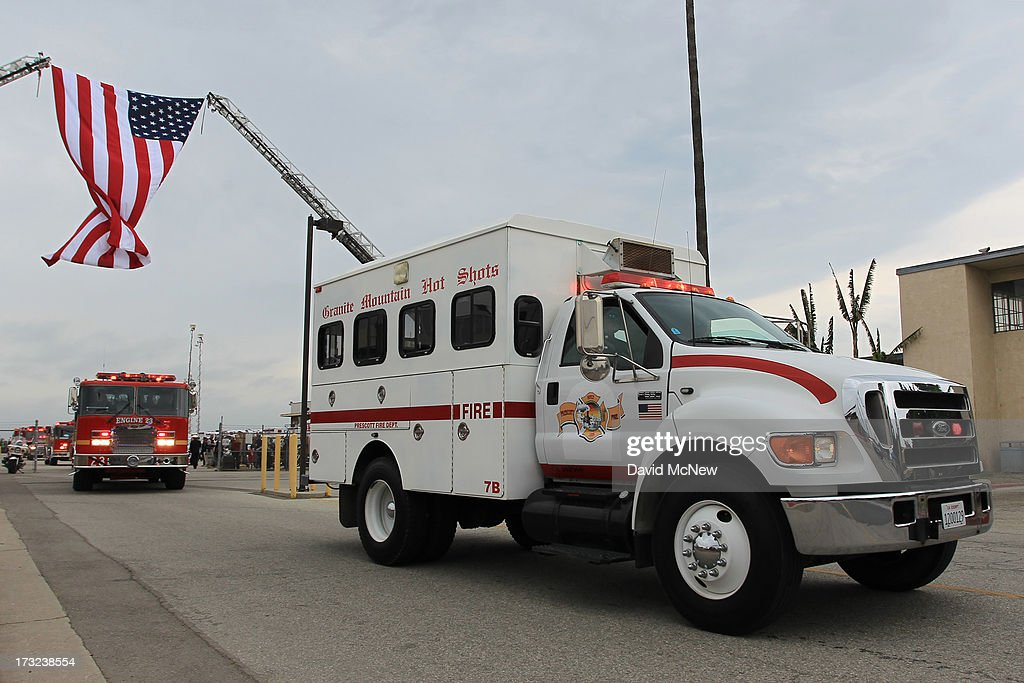 The Granite Mountain Interagency Hotshot Crew truck drives under a flag after two of the nineteen firefighters killed fighting the Yarnell Fire in Arizona arrive to the Joint Forces Training Base, Los Alamitos Air Field on July 10, 2013 in Los Alamitos, California. The memorial ramp ceremony, coordinated in part by the California Fire Foundations Last Alarm Service Team, honors Granite Mountain Interagency Hotshot Crew members 21-year-old Kevin Woyjeck and 20-year-old Christopher MacKenzie.