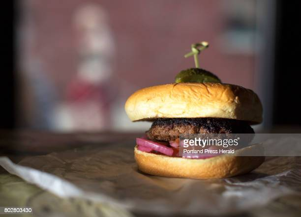 The Grassfed Burger at Mash Tun 29 Wharf St Portland is cooked medium and served on a brioche bun with tart pickled onions a tomato and a gherkin...