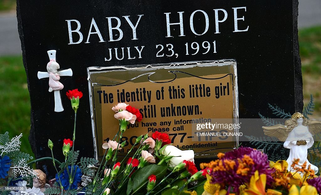 The grave of 'Baby Hope,' an unidentified girl whose body was found murdered in a picnic cooler 22 years ago, is adorned with flowers at St. Raymond Cemetery in New York, October 11, 2013. New York police have at last identified a little girl who was murdered, sexually abused and stuffed into a picnic cooler in Manhattan. She was found on July 23, 1991. New York police officials confirmed the identity of the girl's mother through DNA testing on October 8, 2013, and also identified the father. The family is Mexican and her mother was too frightened to come forward after her daughter's death, because her husband was abusive, local media reports said. The girl's father, who is believed to be either in New York or Mexico, is now the prime suspect. Baby Hope, two years after she was found, was laid to rest in a donated plot. AFP PHOTO/Emmanuel Dunand
