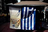 The Greek flag and a towel depicting a 200 Euro banknote hang outside a kiosk in Athens on March 22 2015 The German Chancellor Angela Merkel will...