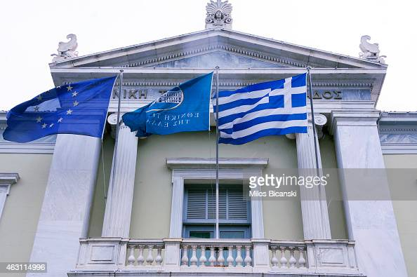 The Greek national bank and EU flags fly at the National Bank building on February 10 2015 in Athens Greece The new Greek antiausterity government is...