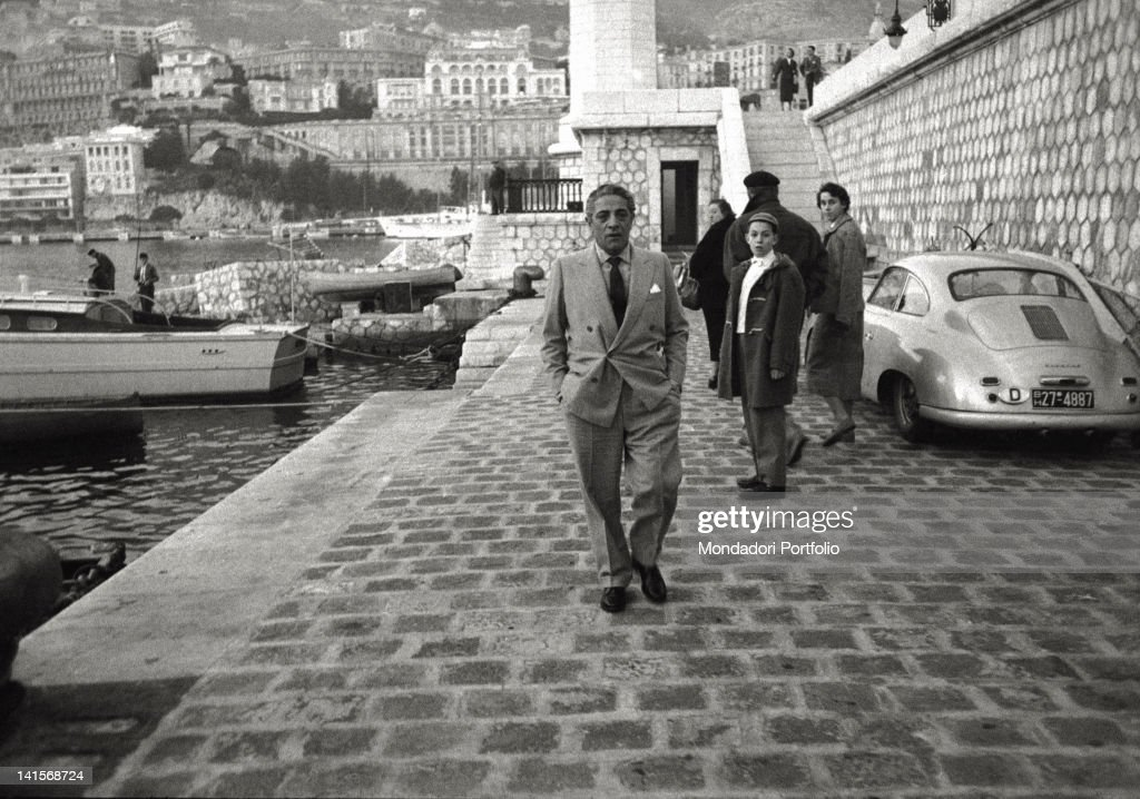 The Greek shipowner <a gi-track='captionPersonalityLinkClicked' href=/galleries/search?phrase=Aristotle+Onassis&family=editorial&specificpeople=217821 ng-click='$event.stopPropagation()'>Aristotle Onassis</a>, known by a family of tourists, photographed on the mole of Montecarlo's port, near the lighthouse; the Principality becomes his official residence by years. Montecarlo (Principality of Monaco), June 1961.