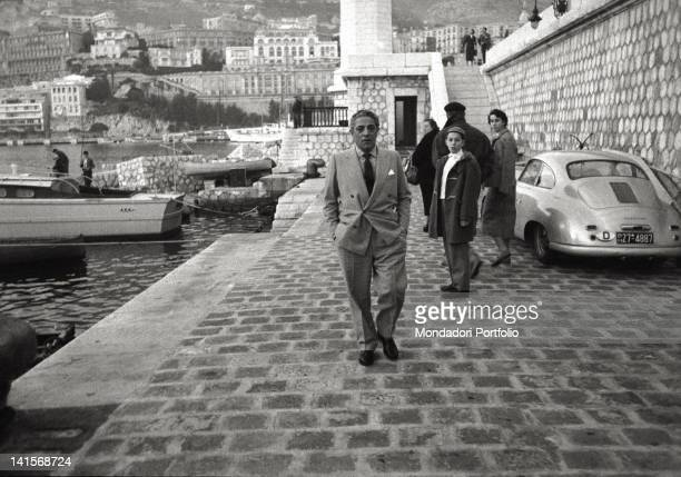 The Greek shipowner Aristotle Onassis known by a family of tourists photographed on the mole of Montecarlo's port near the lighthouse the...