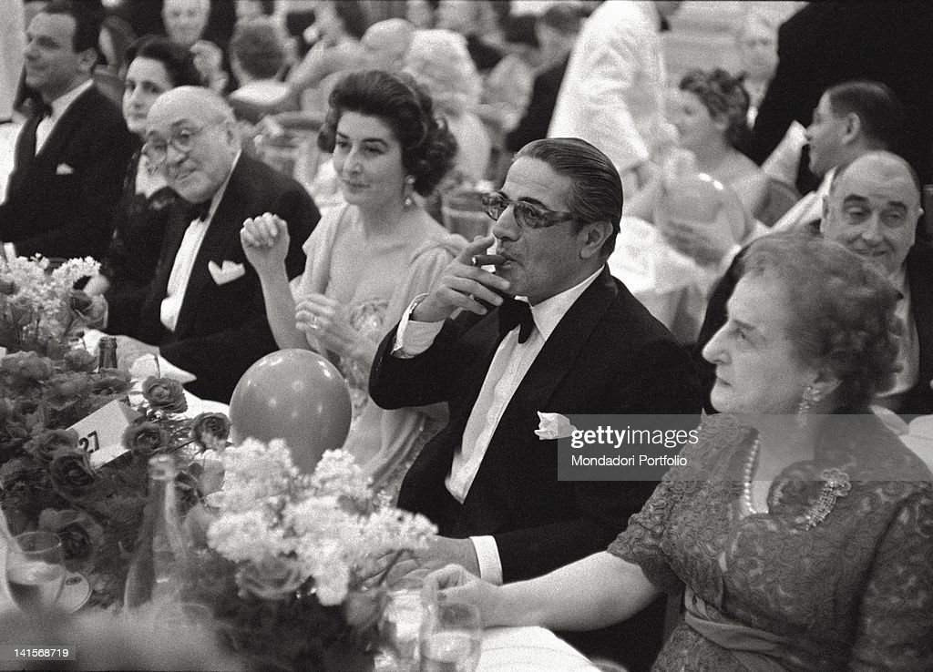 The Greek shipowner <a gi-track='captionPersonalityLinkClicked' href=/galleries/search?phrase=Aristotle+Onassis&family=editorial&specificpeople=217821 ng-click='$event.stopPropagation()'>Aristotle Onassis</a> smoke a cigar to the waiter during an elegant dinner in a restaurant in Montecarlo, by that time his official residence; Onassis docked his own huge yacht 'Christina' on the Principality port, he lives alone to the divorce from his wife and go out with the singer Maria Callas. Montecarlo (Principality of Monaco), June 1961.