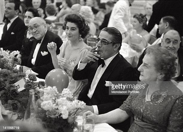 The Greek shipowner Aristotle Onassis smoke a cigar to the waiter during an elegant dinner in a restaurant in Montecarlo by that time his official...