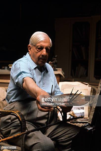 The Greekborn Italian artist Giorgio de Chirico founder of the metaphysical art movement poses with some paint brushes and a palette in his hands...