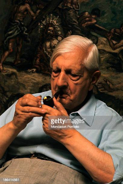 The Greekborn Italian artist Giorgio de Chirico founder of the metaphysical art movement is lighting up his pipe behind him one of his paintings Rome...