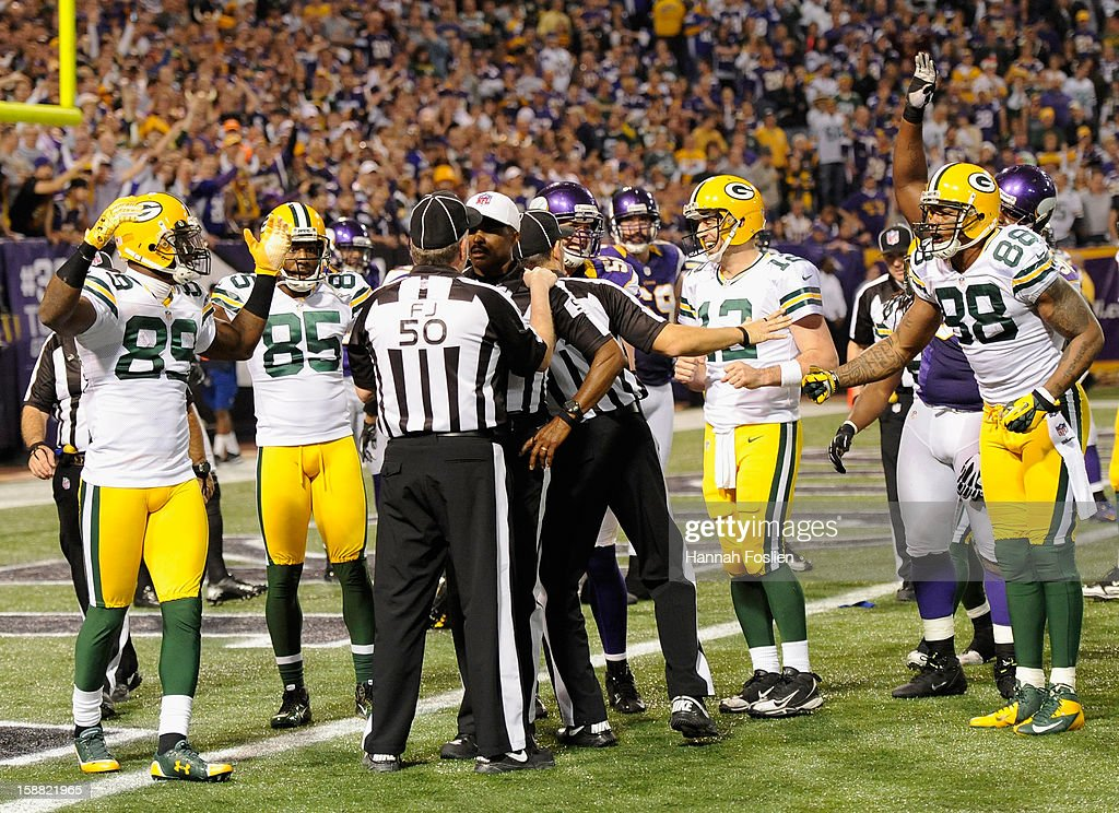 The Green Bay Packers react as field judge Mike Weir #50 speaks with referee Mike Carey #94 after a questionable play in the third quarter of the game against the Minnesota Vikings on December 30, 2012 at Mall of America Field at the Hubert H. Humphrey Metrodome in Minneapolis, Minnesota. The Vikings defeated the Packers 37-34.