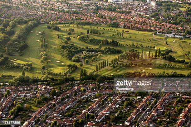 The greens and sand bunkers on Perivale Park golf course are surrounded by rows of residential housing in this aerial photograph taken over Greenford...