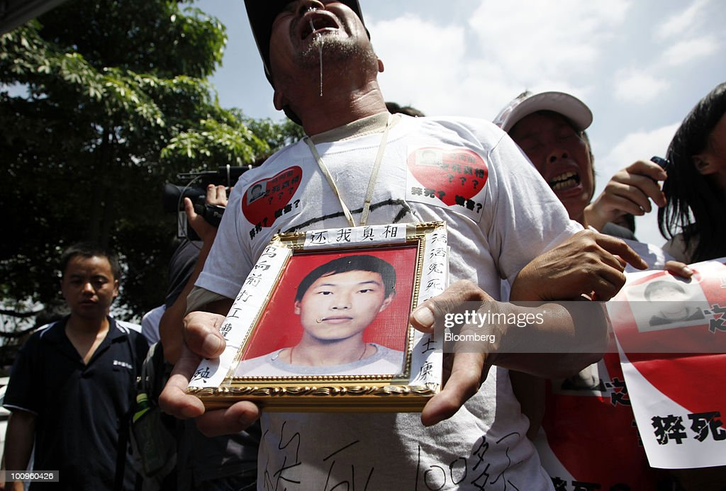 The grieving family members of Ma Xiangqian cry outside Hon Hai Group's Foxconn plant in Shenzhen, Guangdong province, China, on Wednesday, May 26, 2010. Gou said nine of the 11 company workers who either committed suicide or attempted to had worked at the company less than a year, and six had been employed for less than a half-year. Photographer: Qilai Shen/Bloomberg via Getty Images