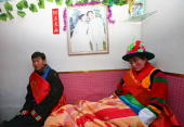 The groom Qi Xinghe and bride Luo Jinhua rest in the bridal chamber during a Tu ethnic minority group wedding ceremony on January 30 2007 in Huzhu...