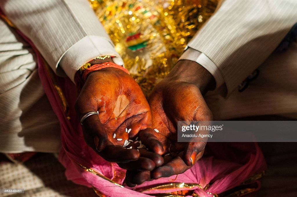 The groom with the rice in his palms which is believed to bring plentifulness, is seen during a wedding ceremony in the outskirts of New Delhi, India on March 13, 2014. Usually around 500 to 1000 guests wearing traditional clothes, attend the traditional wedding ceremony. The ceremony including traditional foods, music and dance, may differ from religion, culture and region.