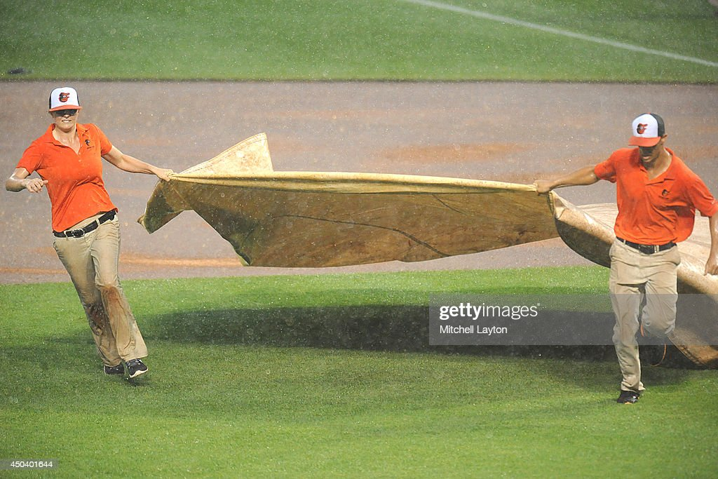 The grounds crew carries out pitching mound tarp during the second rain delay in the second inning of a baseball game between the Baltimore Orioles and the Boston Red Sox on June 10, 2014 at Oriole Park at Camden Yards in Baltimore, Maryland.