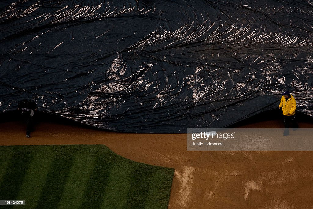 The grounds crew covers the field with the tarp during a rain delay between the New York Yankees and Colorado Rockies at Coors Field on May 9, 2013 in Denver, Colorado.