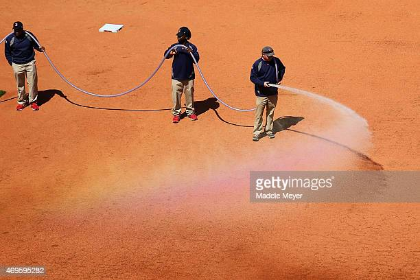 The grounds crew prepares the infield before the game between the Boston Red Sox and the Washington Nationals at Fenway Park on April 13 2015 in...