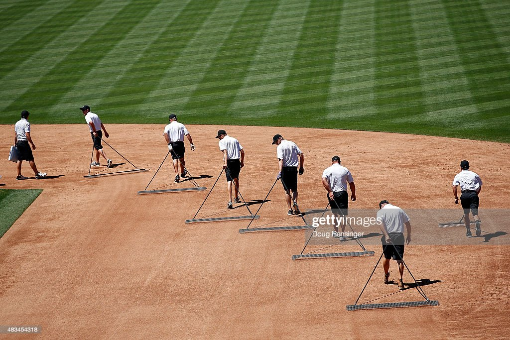 The grounds crew prepares the infield between innings as the Seattle Mariners face the Colorado Rockies during interleague play at Coors Field on August 5, 2015 in Denver, Colorado. The Rockies defeated the Mariners 7-5 in 11 innings.