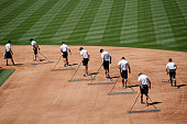 The grounds crew prepares the infield between innings as the Seattle Mariners face the Colorado Rockies during interleague play at Coors Field on...