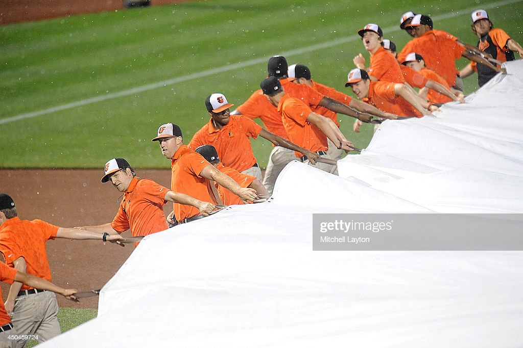 The grounds crew pulls out the tarp during a rain delay in the seventh inning of a baseball game between the Baltimore Orioles the Boston Red Sox on June 11, 2014 at Oriole Park at Camden Yards in Baltimore, Maryland.