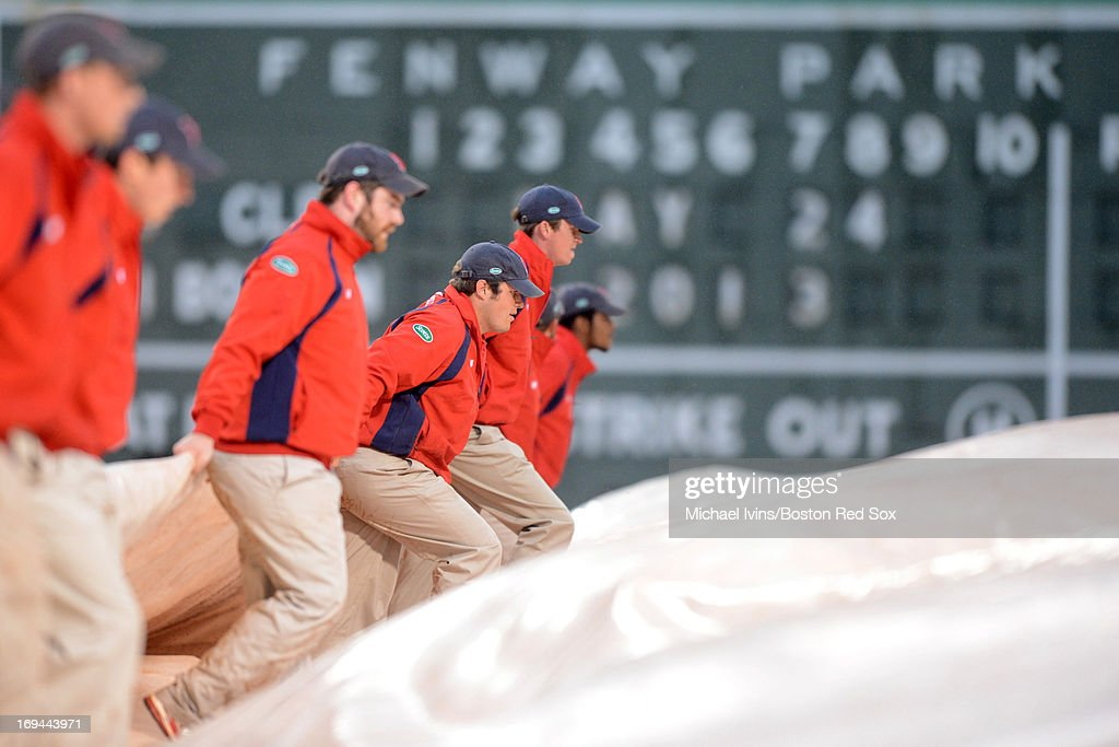 The grounds crew pulls the tarp after rainfall delayed the start of a game between the Boston Red Sox and the Cleveland Indians on May 24, 2013 at Fenway Park in Boston, Massachusetts.