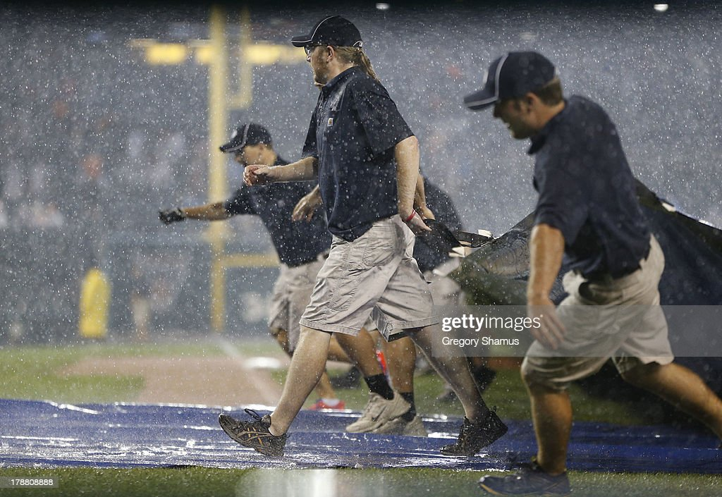 The grounds crew pulls the tarp onto the field during the eighth inning in a game between the Cleveland Indians and the Detroit Tigers at Comerica Park on August 30, 2013 in Detroit, Michigan.