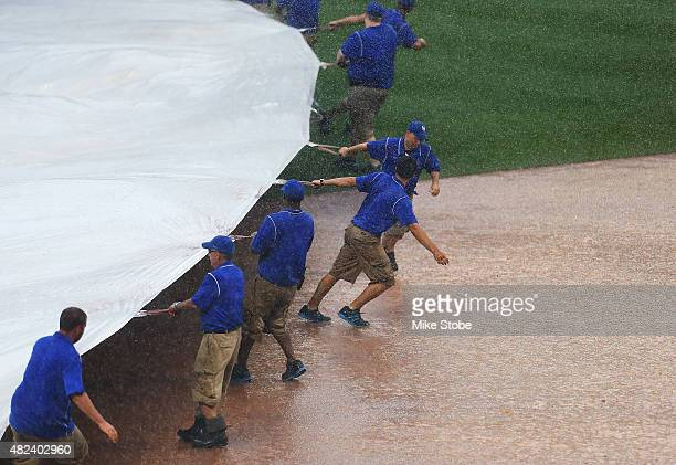 The grounds crew put the tarp on the field for a rain delay in the ninth inning during the game against the San Diego Padres at Citi Field on July 30...