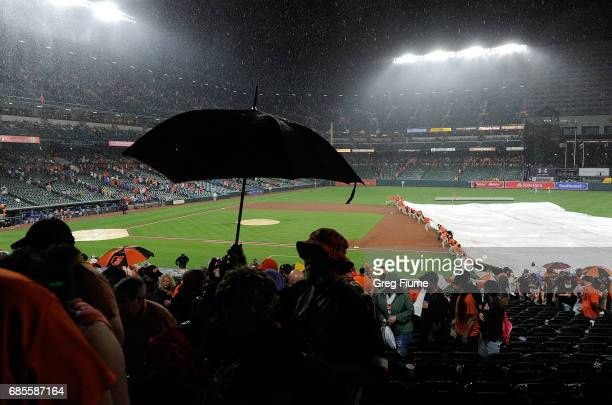 The grounds crew puts the tarp on the field at Oriole Park at Camden Yards in the 10th inning of the game between the Baltimore Orioles and the...