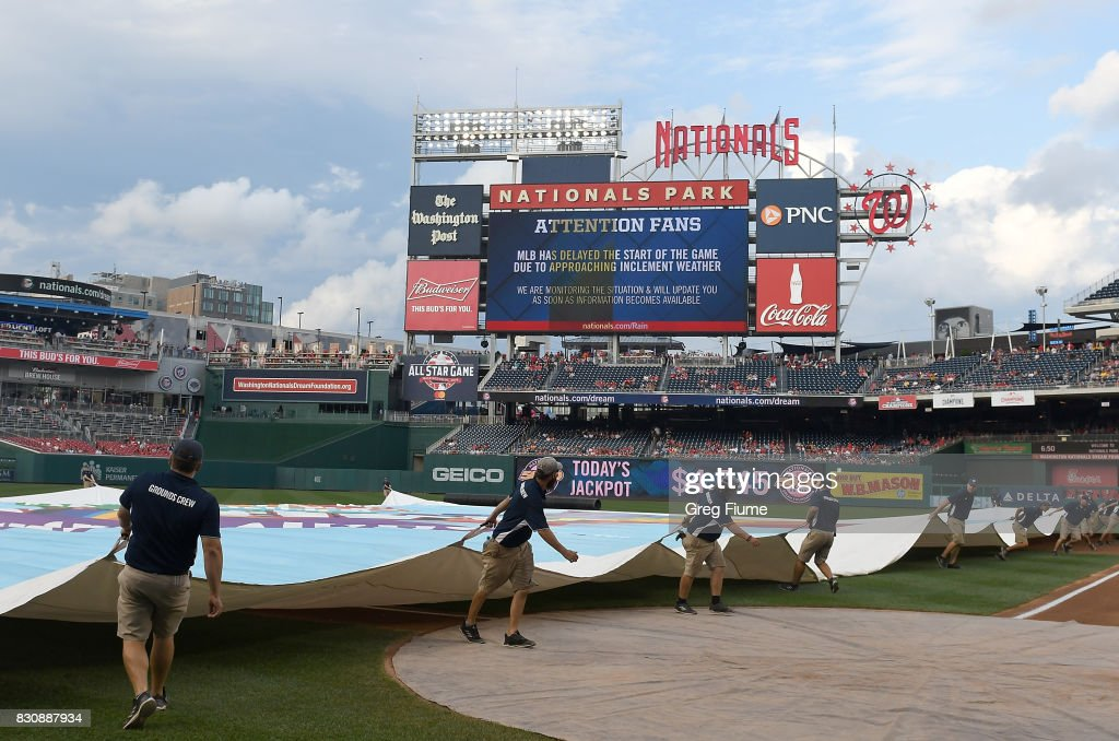 The grounds crew puts the tarp on the field before the game between the Washington Nationals and the San Francisco Giants at Nationals Park on August 12, 2017 in Washington, DC. The start of the game has been delayed.