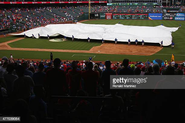The grounds crew puts the tarp on the infield as rain stops the game between the Minnesota Twins and the Texas Rangers in the seventh inning at Globe...