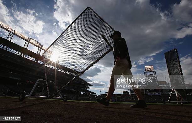 The grounds crew removes the batting practice equipment as Colorado Rockies host the the New York Mets at Coors Field on May 2 2014 in Denver...