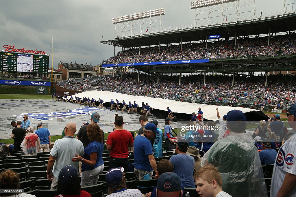 The grounds crew removes the tarp from the infield following a rain delay during the seventh inning as the Chicago Cubs play host to the Philadelphia Phillies on Friday, May 27, 2016, at Wrigley Field in Chicago.