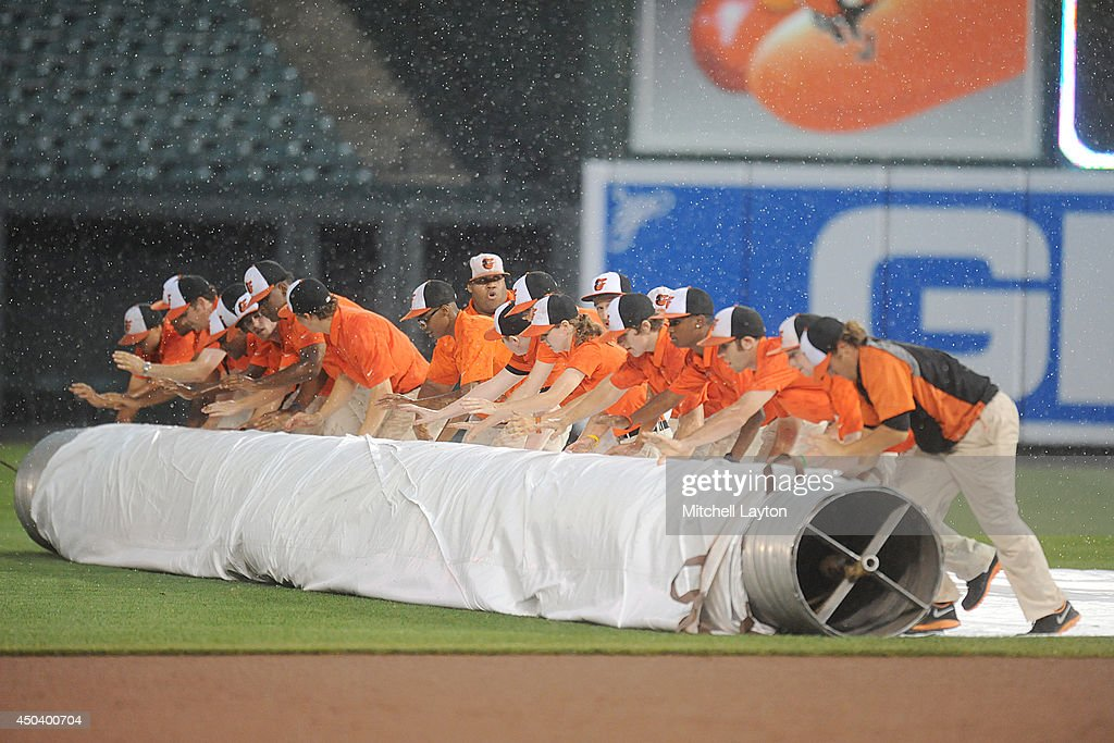 The grounds crew rolls out the tarp during a rain delay in the second inning during a baseball game between the Baltimore Orioles and the Boston Red Sox on June 10, 2014 at Oriole Park at Camden Yards in Baltimore, Maryland.