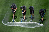 The grounds crew squeegee water out of left field after removing the tarp as rain delayed the start of the game between the San Francisco Giants and...