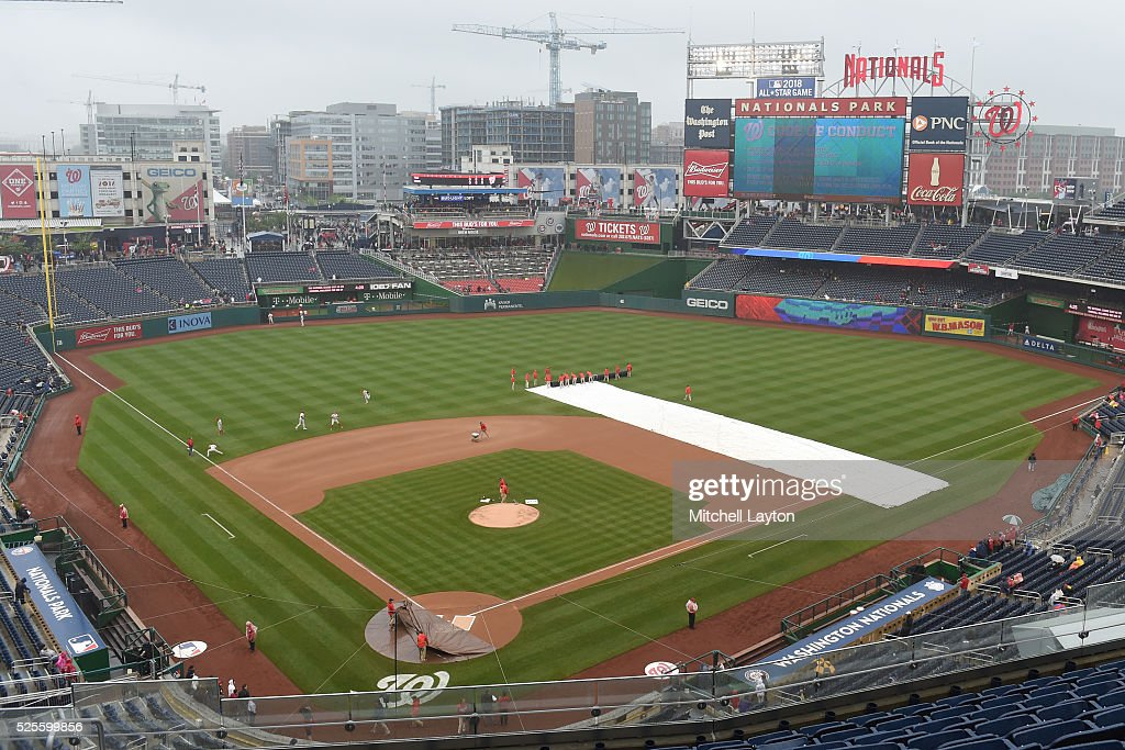 The grounds crew uncovers the tarps after a rain delay start before a baseball game between the Washington Nationals and the Philadelphia Phillies at Nationals Park on April 28, 2016 in Washington, D.C.