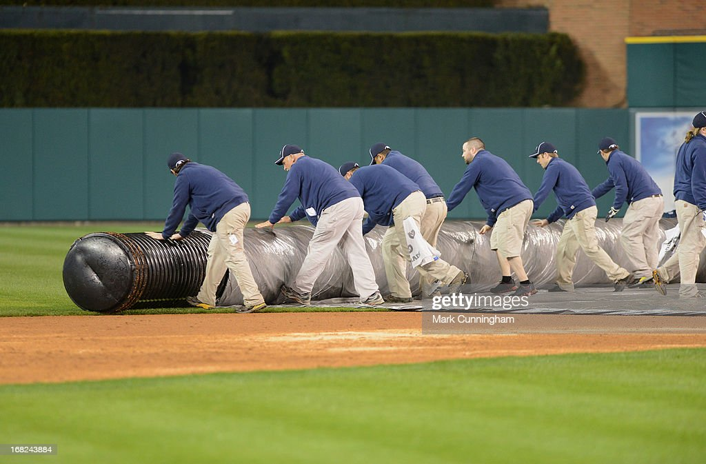 The grounds crew unrolls the tarp onto the field after the game between the Detroit Tigers and the Atlanta Braves at Comerica Park on April 28, 2013 in Detroit, Michigan. The Tigers defeated the Braves 8-3.
