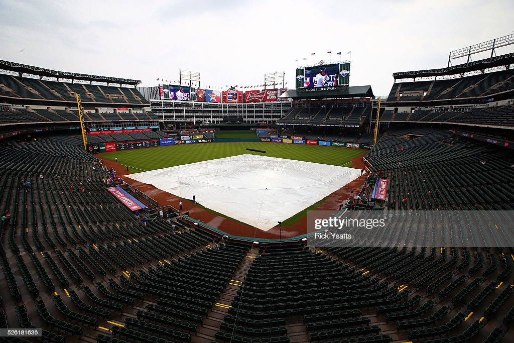 The grounds crew work to remove the water from the tarp before the game between the Los Angeles Angels of Anaheim and the Texas Rangers at Global Life Park in Arlington on April 29, 2015 in Arlington, Texas.