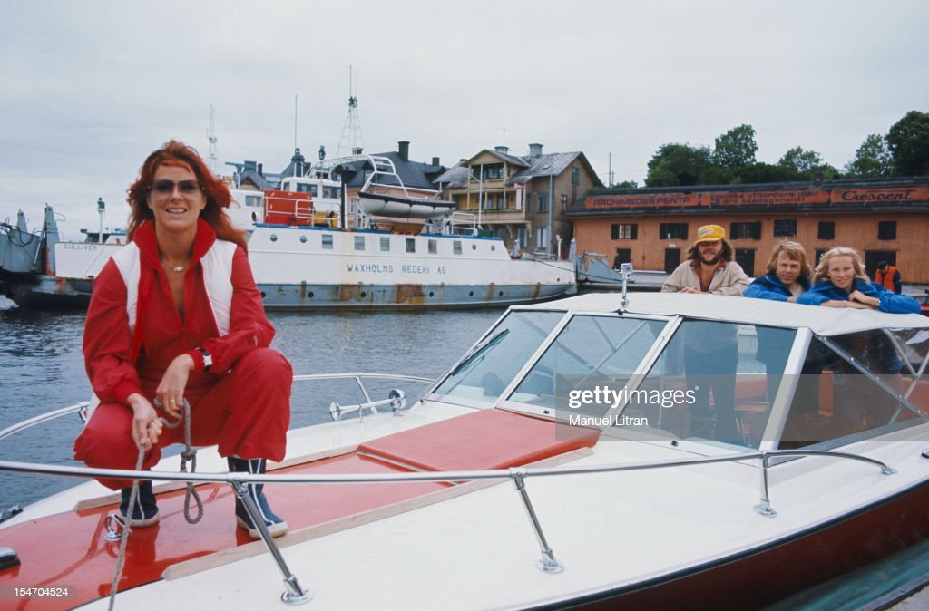 The group ABBA on a boat anchored in a port: smiling attitude of Anni-Frid Lyngstad (Frida called) in the front, rope in hand, standing in the back and her husband Benny Andersson (cap), Bjorn Ulvaeus and his wife Agnetha Faltskog (blue).
