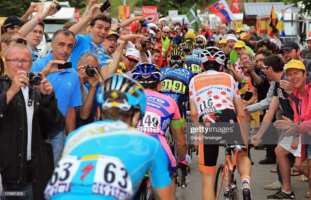 The group of Alberto Contador of Spain riding for Team Saxo-Tinkoff, Mikel Nieve of Spain riding for Euskaltel-Euskadi, Jose Serpa of Columbia riding for Lampre-Merida and Jakob Fuglsang of Denmark riding for Astana make their way through the crowds on the second climb of l'Alpe-d'Huez during stage eighteen of the 2013 Tour de France, a 172.5KM road stage from Gap to l'Alpe d'Huez, on July 18, 2013 in Alpe d'Huez, France.