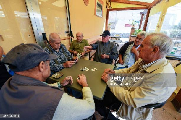 The group old man playing cards out bar in Acciaroli southern Italy Situated on the western coast of southern Italy the town of Acciaroli has a...