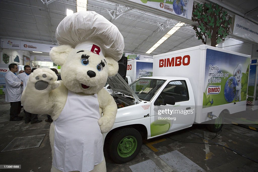 The Grupo Bimbo SAB de CV bear cub mascot waves to attendees in front of the company's new electric delivery trucks inside the company's new sales center in Mexico City, Mexico, on Thursday, July 18, 2013. Grupo Bimbo inaugurated a new eco-friendly sales center today. Photographer: Susana Gonzalez/Bloomberg via Getty Images