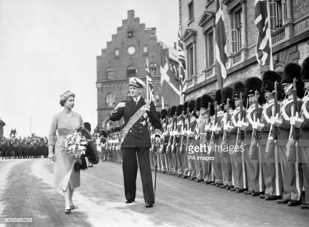 The guard of honour presents arms as Queen Elizabeth II passes with King Frederik IX of Denmark on her arrival with the Duke of Edinburgh in...