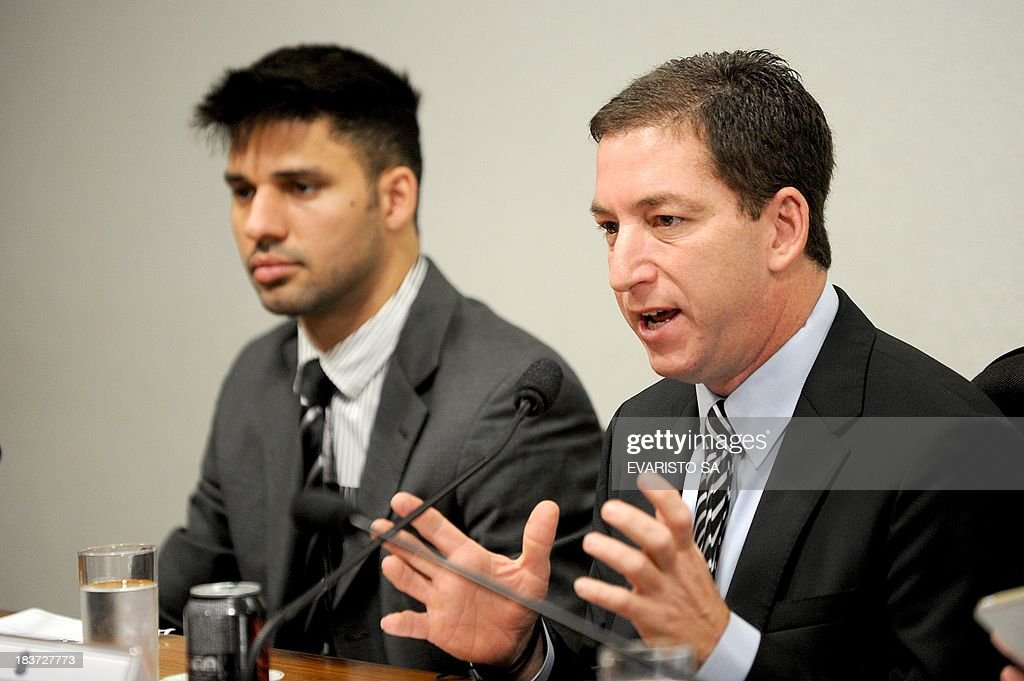 The Guardian's Brazil-based reporter Glenn Greenwald (R), who was among the first to reveal Washington's vast electronic surveillance program, accompanied by his partner David Miranda testifies before the investigative committee of the Senate that examines charges of espionage by the United States in Brasilia on October 9, 2013, following press reports of US electronic surveillance in Brazil based on leaks from Edward Snowden, a former US National Security Agency contractor. AFP PHOTO/Evaristo Sa