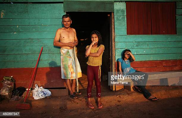 The Guerra family poses in front of their home in a deforested section along the Interoceanic Highway in the Amazon lowlands on November 16 2013 in...