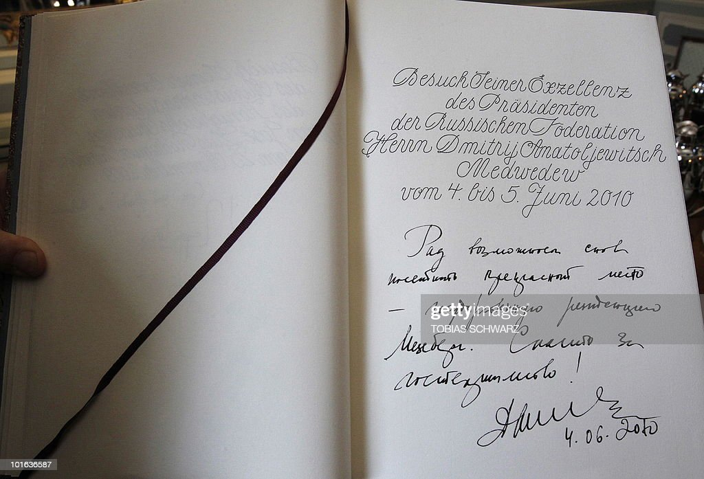 The guestbook entry of Russian President Dmitry Medvedev, written before bilateral talks with German Chancellor Angela Merkel, is presented by an official at the government guest house Schloss Meseberg, some 70 kilometres (43.5 miles) north of Berlin, June 5, 2010. Medvedev is in Germany for two days of what the German government called 'informal' discussions set to be dominated by Iran's nuclear programme and the Middle East.