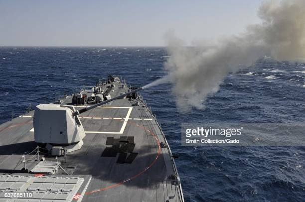 The guidedmissile destroyer USS Jason Dunham fires a MK 45 5 inch 62 caliber lightweight deck gun during a livefire exercise on a Navy ship January...